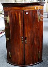 A George III inlaid mahogany bowfront two door corner cupboard, 71cm wide.