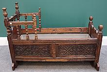 A 17th century carved oak cradle on turned supports, 100cm wide.