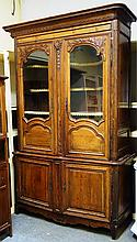 An 18th century French stained pine buffet du coeur, with pair of glazed doors enclosing shaped shelves, over pair of lower panel doors, 153cm wide x 241cm high.