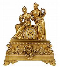 Mantelclock. Firegilt bronze. Clockface set in a stand on which two muses o