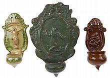 A set of three various holy-water-fonts. The first one in green glazed eart