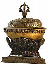 Kapala en bronze de patine médaille, comprenant le récipient avec couvercle surmonté d'un vajra, et un socle ouvragé.  Tibet. Haut. 21,5 cm.  150/250€