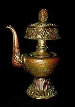 Verseuse à offrande Bumpa en cuivre repoussé avec traces d'argenture, sur pied lotiforme, le bec verseur orné d'un makara, la partie supérieure décorée des huit signes auspicieux et d'une rangée de lotus. Tibet, XVIIIe-XIXe siècles. Haut : 21 cm