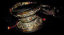 Tambourin rituel, Damaru, formé de deux calottes crâniennes reliées par leur sommet, serties d'argent repoussé à décor des quatre animaux, tigre, dragon, lionne des neiges et garuda et de feuillages stylisés, et rehaussé de turquoise et corail. Tibet