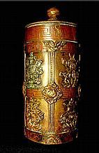Récipient cylindrique Jadung, en cuivre repoussé partiellement doré et argenté, orné des huit signes auspicieux en relief. En deux parties, il était destiné à contenir des pilules et des herbes médicinales. Tibet central, XIXe siècle. Haut : 22 cm