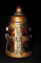 Récipient Jadung, en cuivre et bronze martelé et repoussé, le couvercle surmonté d'une frise et d'un bouton de lotus.  Tibet, XIXe siècle. Haut : 19,5 cm  90/110 €