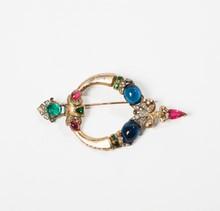 TRIFARI  Broche en argent, sertie de pierres multicolores à l'imitation émeraudes, saphirs et rubis.