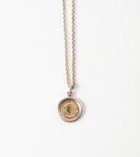 HERMES Paris made in France  Tour de cou en argent retenant un pendentif clou de selle en or jaune et argent.  Pds: 15,5 grs environ.