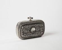 Françoise MONTAGUE  Pochette du soir ornée de petits motifs en métal argenté, de strass entourant une pierre facettée, armatures, fermoir en métal chromé. Non signée.