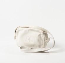 COURREGES Paris  Sac 22 cm en cuir vieilli blanc, devant siglé, fermeture Eclair, anse bandoulière. (Taches)
