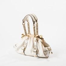 VERSACE  Sac 30 cm en toile siglée blanche et cuir grené à la couleur, armature rigide, attaches et fermoir en métal doré, anses chaînes retenant des pattes d'épaules. Bon état (taches).