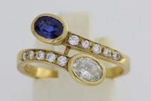 Bague Toi et Moi en or ornée d'un saphir et d'un diamant ovale épaulés de lignes de brillants. P. 3,8g