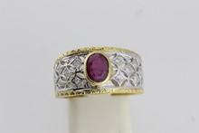 Bague en or de deux couleurs ajouré ornée d'un rubis central épaulé de diamants. P. 7,6g