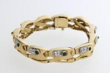 Bracelet en or articulé enrichi d'émeraudes cabochons et de diamants. P. 53g