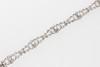 Bracelet articulé en or et platine à décor de naeuds et de guirlandes sertis de diamants. P 19,9g