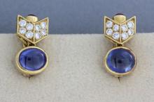 BULGARI. Paire de boucles d'oreilles en or jaune ornées d'un cabochon de saphir retenant un motif pavé de brillants se terminant par un cabochon de rubis. P. 11,5G