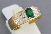 FRED. Bague en or ornée d'une émeraude ovale épaulée de 12 diamants baguettes. P. 7,1g
