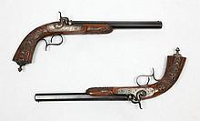 Belle paire de pistolets de duel à percussion, calibre 10,4 mm. Canons à pans, bleuis, rayés, gravés aux tonnerres ainsi que aux queues de culasse. Platines avants à corps plats, chiens à corps ronds; l'ensemble gravé de rinceaux feuillagés. Pontets