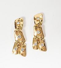 Christian LACROIX    Paire de pendants d'oreilles en métal doré de forme géométrique mouvementé sertis de strass à l'imitation brillant. Signé.