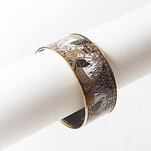 HERMES Paris made in Austria    Large bracelet jonc en métal doré émaillé noir à décor de têtes de chevaux. Diamètre : 7cm.