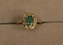 Ring  -  facetted oval emerald (approximately 1ct) surrounded by9 small white diamonds
