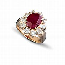 Une bague dite « entourage » en or jaune (14K, 550‰) sertie d'un rubis traité de taille ovale dans un entourage de dix diamants de taille brillant pesant chacun environ 0,08 carat.