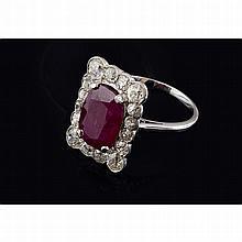 Une bague en or gris (18K, 750‰) et platine (900‰) de forme rectangulaire sertie d'un rubis de taille coussin pesant environ 4,14 carats entourage de diamants de taille ancienne dans un serti perlé.
