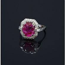 Une bague en or gris (18K, 750‰) sertie dans un entourage de diamants de taille ancienne d'un rubis de forme coussin, l'anneau partiellement orné de diamants calibrés.