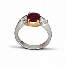 Une bague en or deux tons (18K, 750‰) ornée d'un rubis de taille ovale, épaulé de deux diamants taillés en coeur.