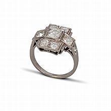 Une bague en platine (900 ‰) de forme géométrique sertissant 7 diamants de taille ancienne épaulés de petits diamants dans un serti perlé.