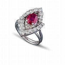 Une bague marquise en or gris (18 K, 750 ‰) ornée en son centre un rubis serti à griffes,  dans un entourage serti de diamants brillantés.