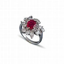 Une bague en or gris (18 K, 750 ‰) ornée en son centre un rubis de taille ovale serti à griffes, dans un entourage asymétrique serti de diamants brillantés.
