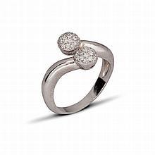 Une bague « Toi & Moi » en platine (900 ‰) ornée de deux demies sphères serties d'un pavage de diamants brillantés.