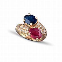 Une bague « Toi & Moi » en or jaune (18K, 750‰) sertie d'un rubis ovale traité pesant environ 2,40 carats et d'un saphir ovale pesant environ 2,70 carats épaulés d'un pavage de diamants brillantés.