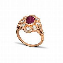 Une bague en or jaune (18K, 750‰) ornée d'un rubis ovale dans un entourage de huit diamants de taille brillant en serti clos.