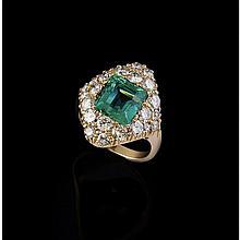 Une bague en or jaune (18K, 750‰) de forme losangique le corps serti de diamants de taille brillant, ornée en son centre d'une émeraude taillée à degrés pesant environ 3,60 carats.