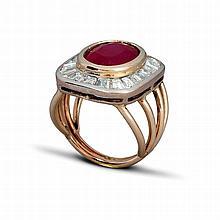 Une bague en or gris (18K, 750‰) l'anneau scindé en quatre soutenant un motif central de forme carrée orné en son centre d'un rubis traité de forme coussin en serti clos cerné d'une ligne de diamants calibrés.