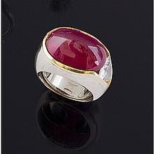 Une bague jonc en or deux tons (18K, 750‰) sertissant un important rubis taillé en pain de sucre d'environ 13,50 carats bordé sur un coté d'un diamant troïdia serti dans l'anneau.
