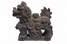 A black/grey terracotta roof ornament in de shape
