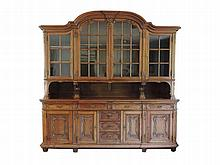 A Liege-style oak display cupboard with shaped cornice,two large and two short glass paneled cupboard doors, above four frieze slides above seven drawers and four panelled cupboard doors with shaped panels and rocaille carving 288,5 x 290 x 74 cm.,