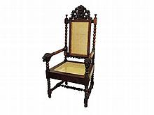 An oak armchair the back with shaped top, turned armrests terminating in lion's masks late 19th Century