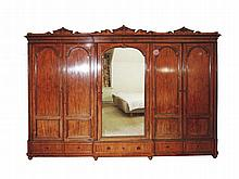 A German mahogany cupboard with shaped cornice central mirror panelled door opening to an interior with six slides flanked by four cupboard doors with arched panels, the base with one long and two short drawers late 19th Century 245 x 366 x 85 cm.