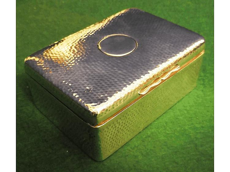 A heavy hand-hammered silver cigarette box