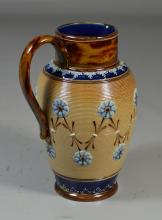 Doulton Lambeth tan and brown pitcher with relief blue floral design, 8 1/2