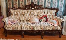Carved Victorian style sofa with spread wing eagle crests, tufted floral upholstery, 82