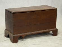 Dovetailed walnut blanket chest, top with mitered breadboard ends, raised on dovetailed straight bracket feet, right front foot miss...