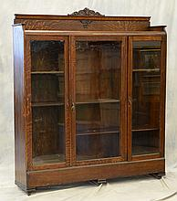 American oak triple door bookcase with carved crest, 69