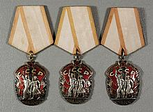 (3) Soviet red enameled medals depicting a couple walking carrying banners, on a peach colored ribbon, overall ht about 4