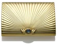 A sapphire and fourteen karat gold starburst design compact
