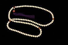 A STRAND  108 IVORY AND AMBER PRAYER BEADS